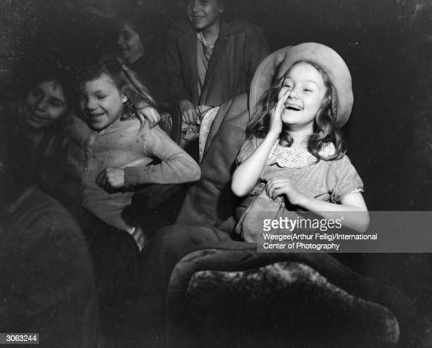 A little girl laughs out loud at a film Using infrared film Photo by Weegee/International Center of Photography/Getty Images