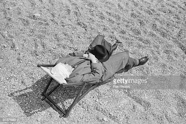 A man relaxing at the seaside on a sunny day in April He has a handkerchief over his head to protect him from the sun but is still wearing his...