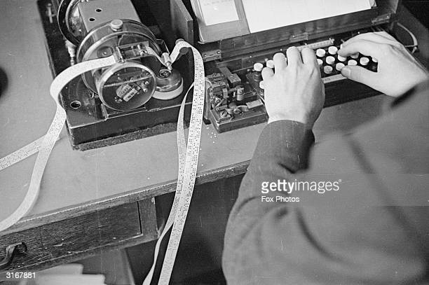 A man using a ticker tape machine attached to a typewriter keyboard at a Press Association and Reuters office