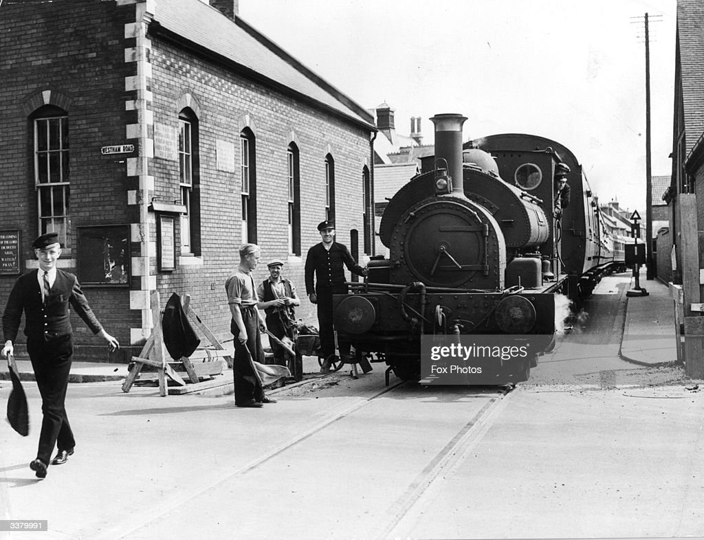 A man with a red flag walking in front of a steam train at a