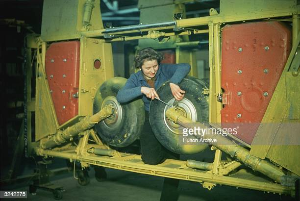 A member of the ATS mends the undercarriage of a Hawker Hurricane