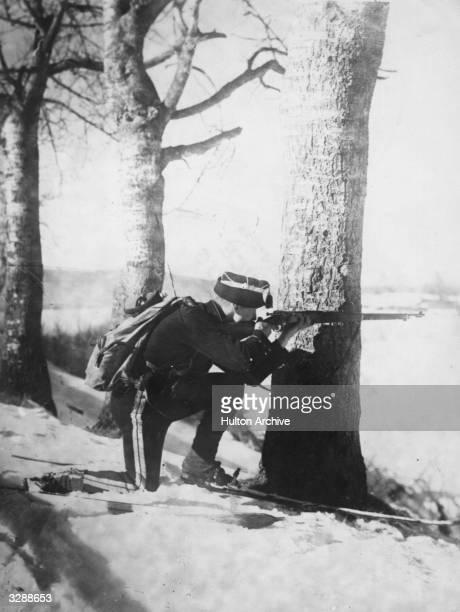 A Norwegian Royal Trooper wearing skis kneels down and takes aim