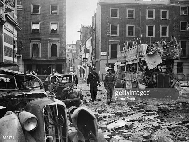 A policeman and a soldier of the Home Guard walk past vehicles wrecked during a German bombing raid near Marble Arch London