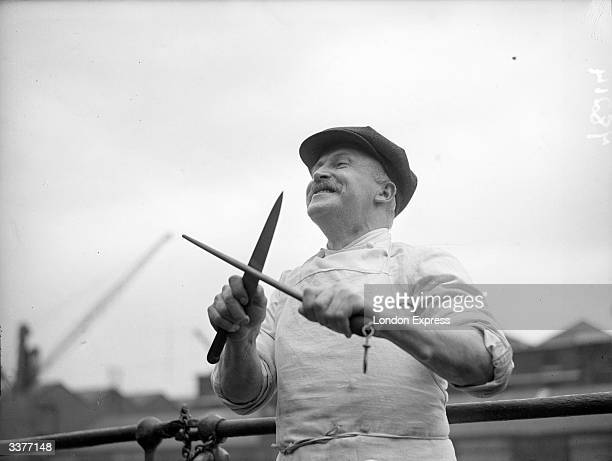 A ship's cook sharpening a carving knife His ship is safely in port after being shelled at sea during which time he kept on cooking a midday meal