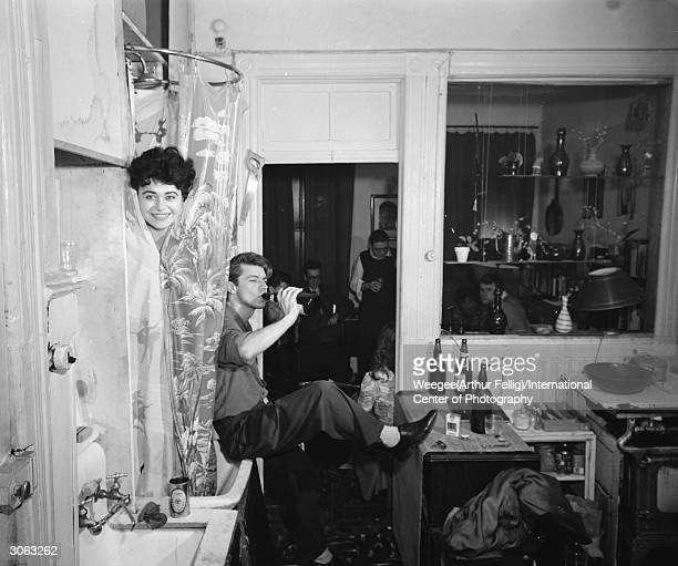 A smiling woman peeks out from behind a shower curtain at a house party Photo by Weegee/International Center of Photography/Getty Images