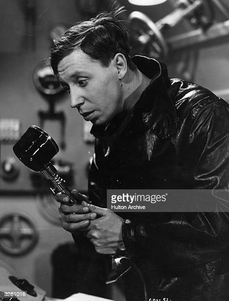 A waterproof clad man probably George Formby in an engine room seems very apprehensive about a what appears to be a microphone he is holding