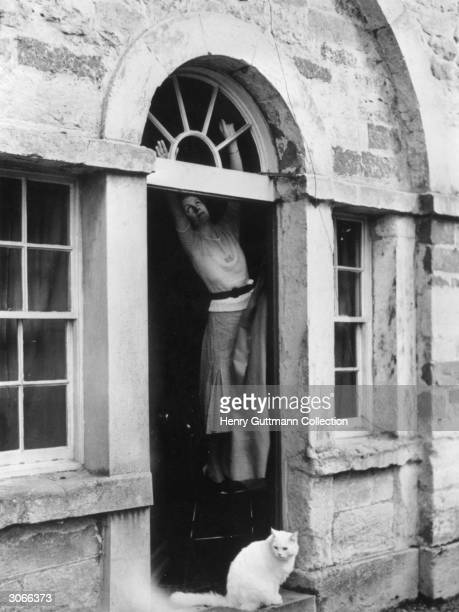 A woman hangs dark material over the window above her front door in preparation for a World War II blackout