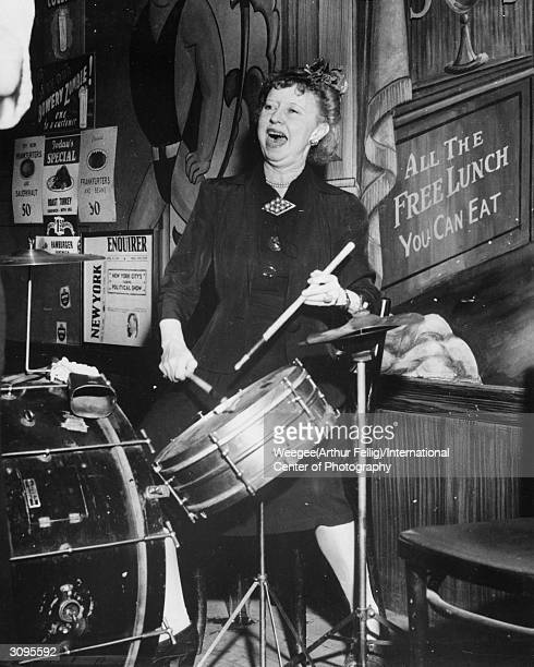 A woman playing the drums in front of a sign advertising 'all the free lunch you can eat' Photo by Weegee/International Center of Photography/Getty...