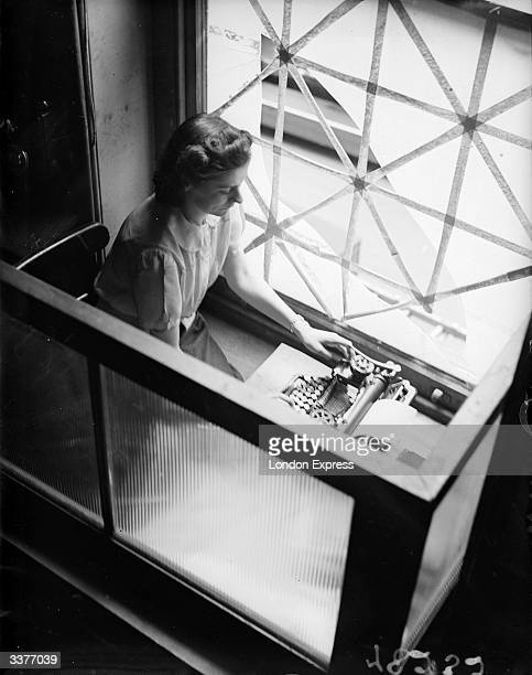 Woman typing by a window criss-crossed with sticky tape to prevent flying glass.