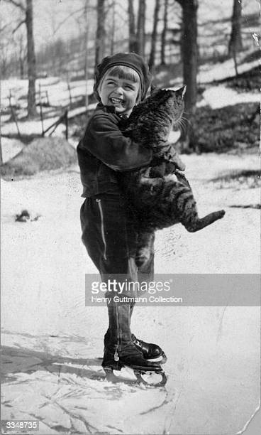A young boy on skates clutches a large tabby cat