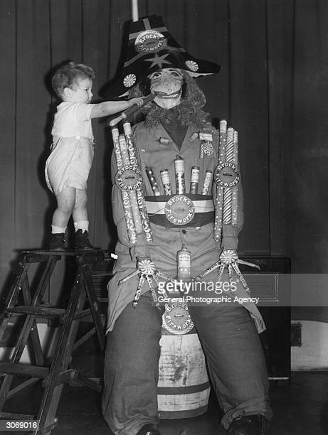 A young toddler adds the finishing touches to an effigy of Guy Fawkes on Guy Fawkes Night