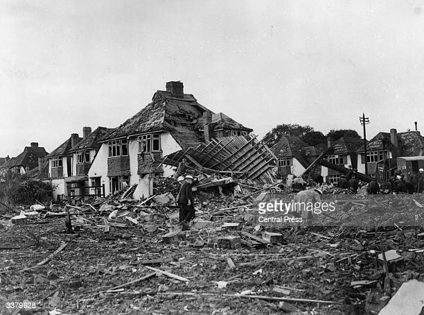 Air raid wardens walk through debris in a residential area in Surrey after a German bombing raid