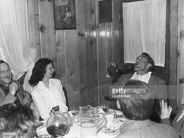 American actor Gary Cooper drinks from a bota while smoking a cigarette in the dining room of the Club Rio in Ketchum Idaho At left is Tillie Arnold...