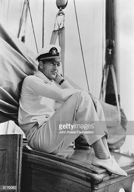 American actor Gary Cooper sitting on board a yacht wearing a sailor's cap