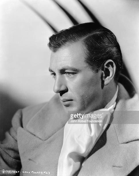 American actor Gary Cooper wearing a winter coat and a cravat.