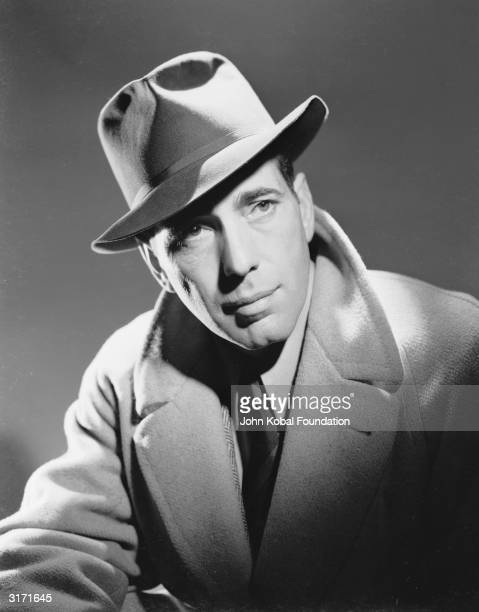 American actor Humphrey Bogart wearing a trilby and overcoat.