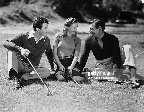 American actress Barbara Stanwyck formerly Ruby Stevens relaxes on a golf course with her husband Robert Taylor and Clark Gable