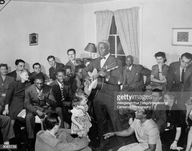 American blues singer and guitarist Huddie Ledbetter better known as Leadbelly performs for a room full of people Photo by Weegee/International...