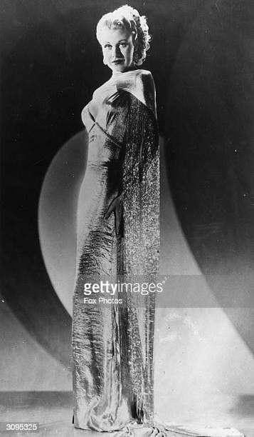 American dancer and actress Ginger Rogers wearing a shiny slimfitting evening gown