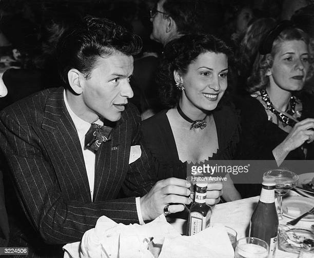 American singer and actor Frank Sinatra sitting at a table in a nightclub next to his first wife Nancy Barbato Sinatra wears a striped suit silk tie...