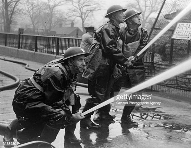 ARP firemen practise directing their hoses at a fire during World War II