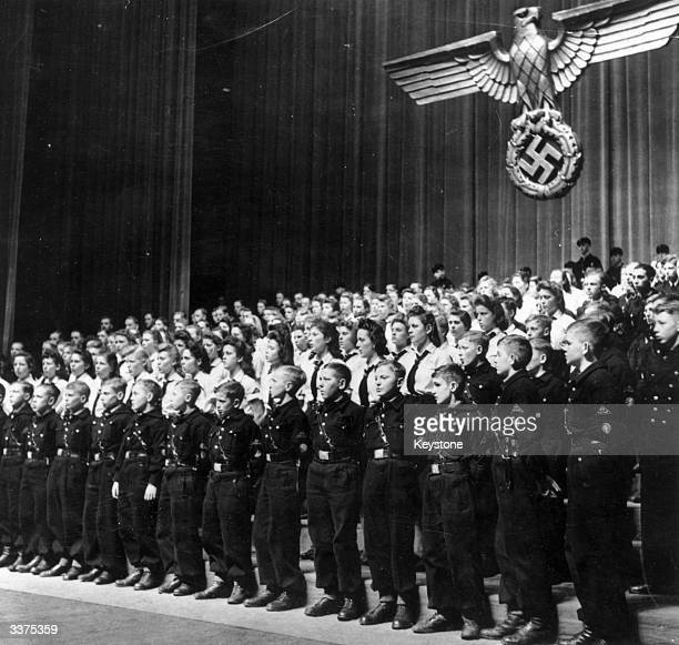 Boys and girls parade on stage at a meeting for the Hitler Youth in Germany.