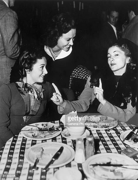 British actress Olivia de Havilland in a restaurant with her sister Joan Fontaine and American actress Margaret Lindsay