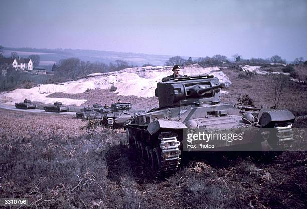 British Army Vickers Valentine infantry tanks make their way over some hilly terrain