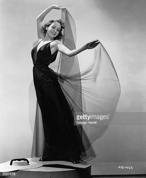 British-born actress Olivia de Havilland raises the skirts of her filmy black dress like wings.
