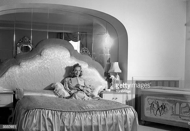 Cabaret star, impersonator, stage and screen actress Florence Desmondrelaxes on her sumptious bed.