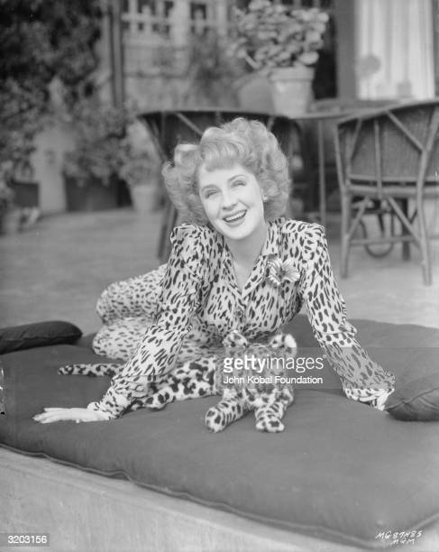 Canadian movie star Norma Shearer wearing a leopard print suit and a bouffant hairdo A matching toy leopard sits in front of her on a cushion