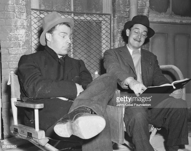 Director Preston Sturges reads a scene out loud to actor Brian Donlevy on the set of 'Down Went McGinty'