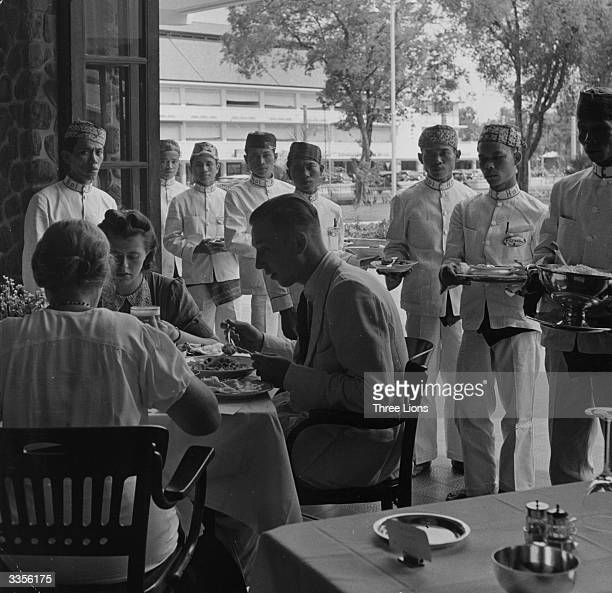 Dutch colonialists eating in Java Indonesia with a group of waiters in attendance