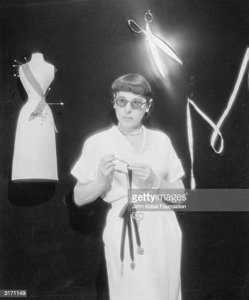 Edith Head standing in front of a wall decorated with a pair of scissors a measuring tape and a model of a mannequin Hollywood's best known and most...