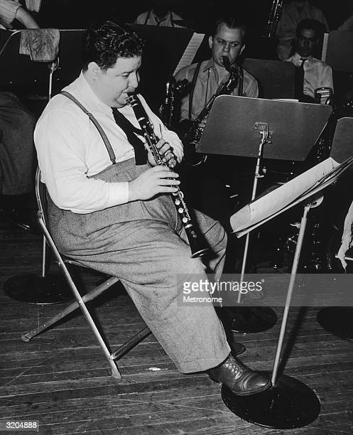 American jazz clarinettist Irving Fazola sits and plays with other musicians in a studio. A saxophonist sits behind Fazola.