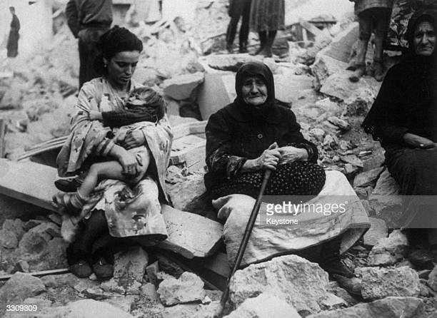 Four generations of Greek peasants amid the ruins of their home.