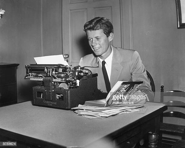 Future American president John F Kennedy sits at a typewriter holding open his published thesis 'Why England Slept'