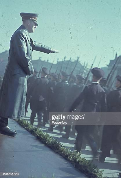 Circa 1940 - German Chancellor Adolf Hitler gives a salute to passing Axis soldiers on parade circa 1940.