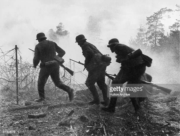 German soldiers running through a field of smoke and barbed wire during a World War II encounter in France.