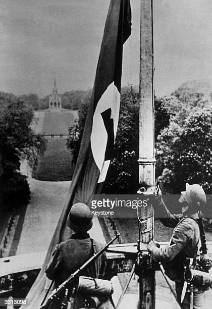 German troops hoisting the Nazi flag on the Royal Castle at Laeken near Brussels after their invasion