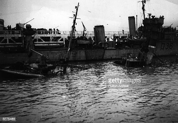HMS 'Valorous' is alongside the pier at Dunkirk next to a trawler which was sunk by a bomb HMS 'Imogen' is on the far side