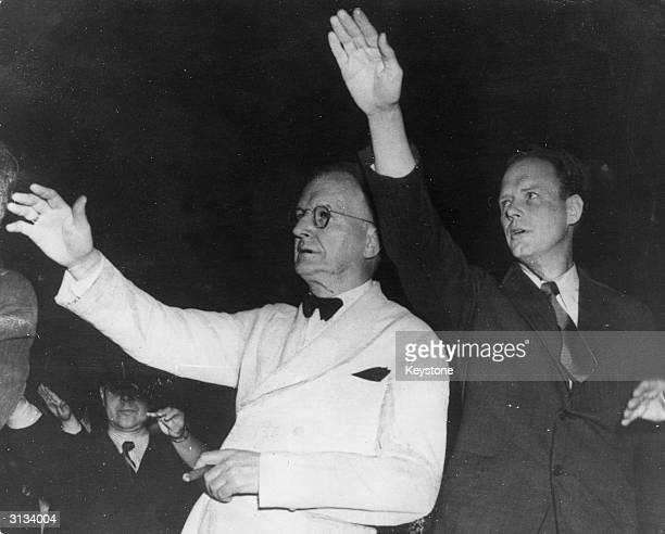 L to r Senator Burton Wheeler of Montana and Colonel Charles Lindbergh saluting the US flag at a rally to keep the US out of WW II