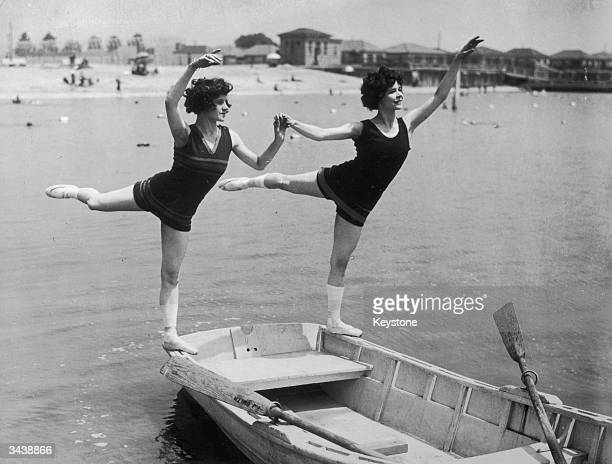 Maide du Fresne and Marion Wilkins risk a soaking by dancing on the edge of a rowing boat on Manhattan beach California