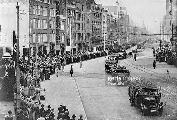 Nazi troops and armoured divisions driving along a main street in Amsterdam on a route from Central Station past the Queen's Palace