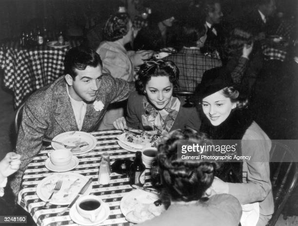Olivia De Havilland leans in to hear a conversation while lunching with her sister Joan Fontaine and actor John Payne