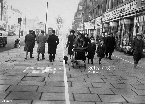 On one of the main thoroughfares of Ealing London the pavement is divided into three sections for the pedestrian traffic with one nearest to the...
