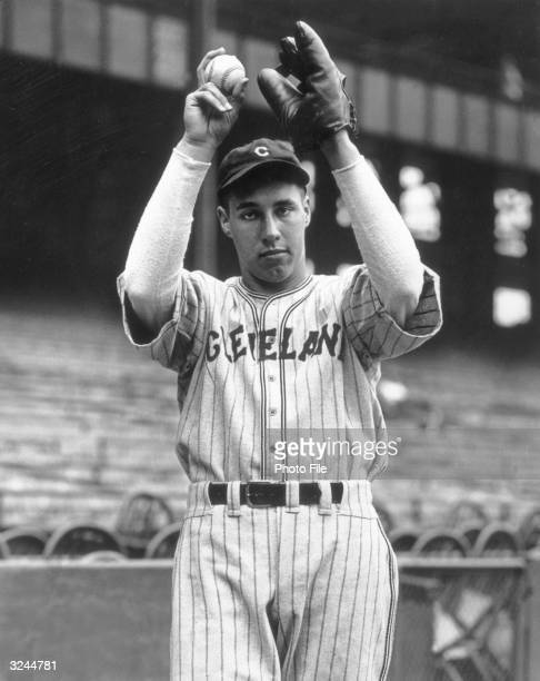 Pitcher Bob Feller of the Cleveland Indians seen here striking an action pose with a ball and mitt above his head while wearing his uniform in a...
