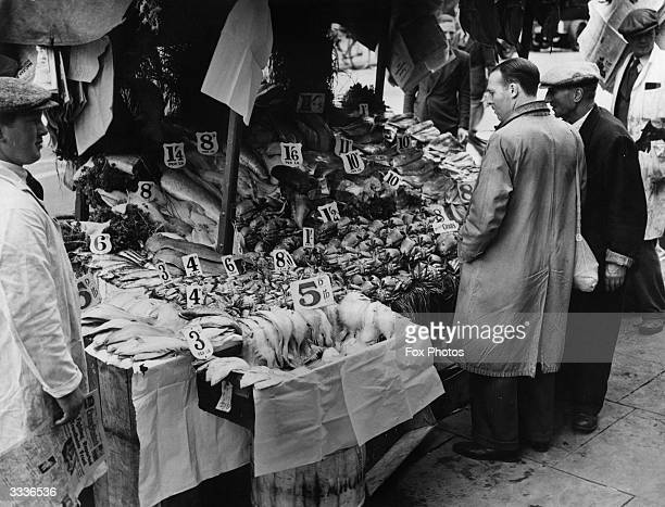 Potential customers at a wellladen fish stall in a London market