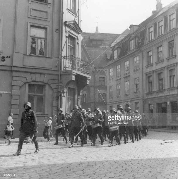 Steel helmetted soldiers playing drums as they march through a street in Riga capital of Latvia during WW II
