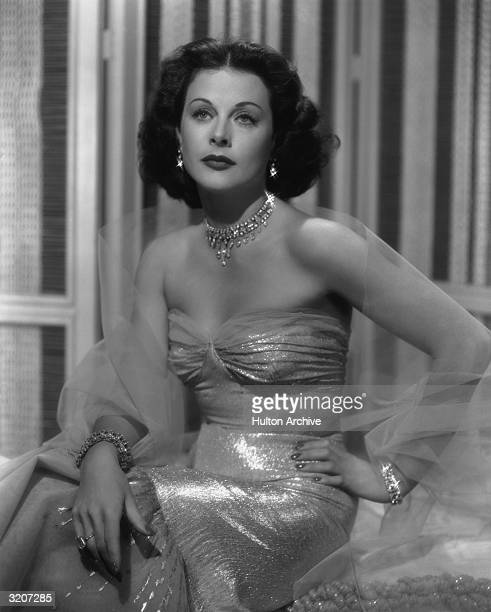 Studio portrait of Austrianborn actor Hedy Lamarr wearing a strapless gown and glittering jewelry sitting with her hand on her hip